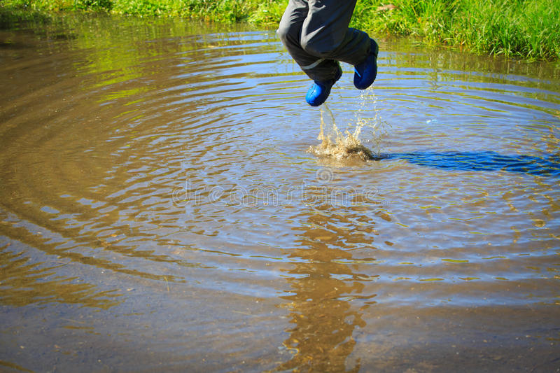 Little Boy In Rain Boots Jumping Into Water Puddle Stock