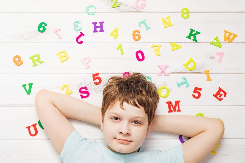 Little boy with rainbow alphabet letters laying on the wooden floor royalty free stock images