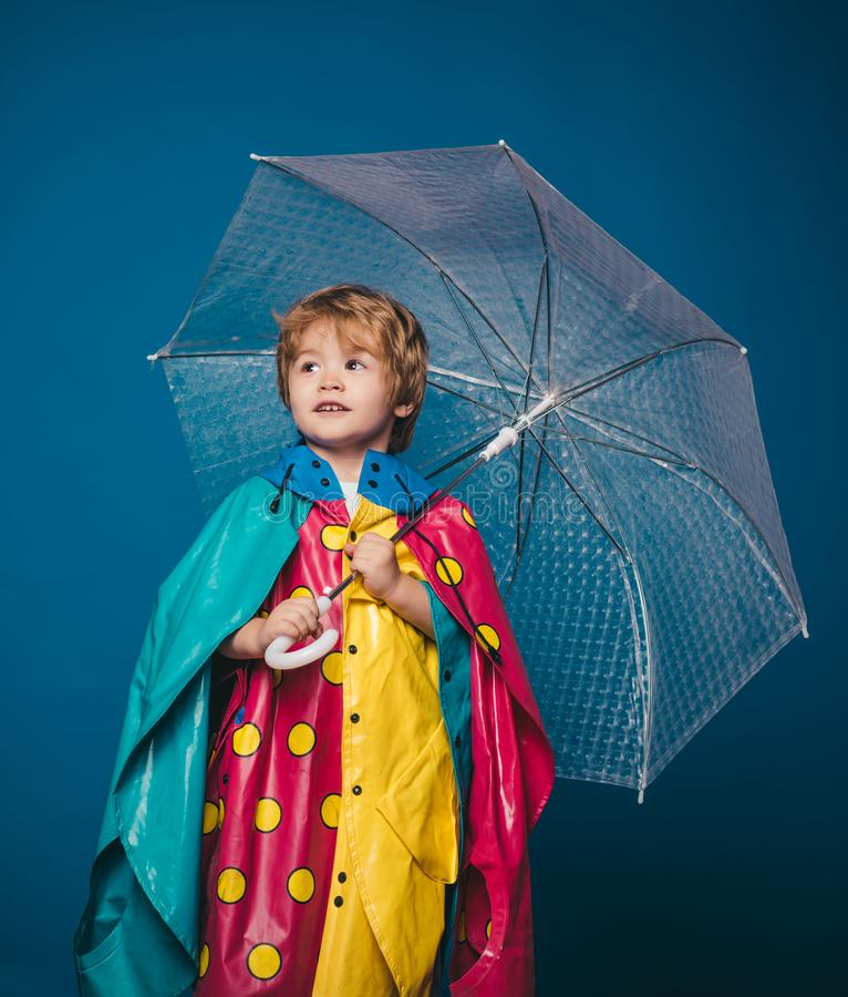 Little boy with rainbow-colored umbrella isolated on blue background. Cloud rain umbrella. Raining concept. Autumn mood stock images