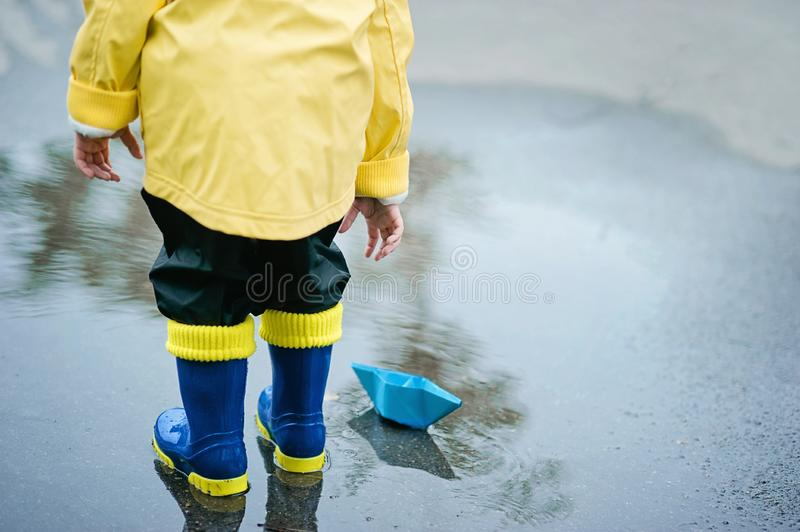 Little boy in raincoat and rubber boots playing in puddle. Happy little kid with paper ship royalty free stock photo