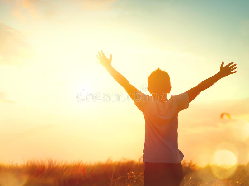 Little boy raising hands over sunset sky royalty free stock photo
