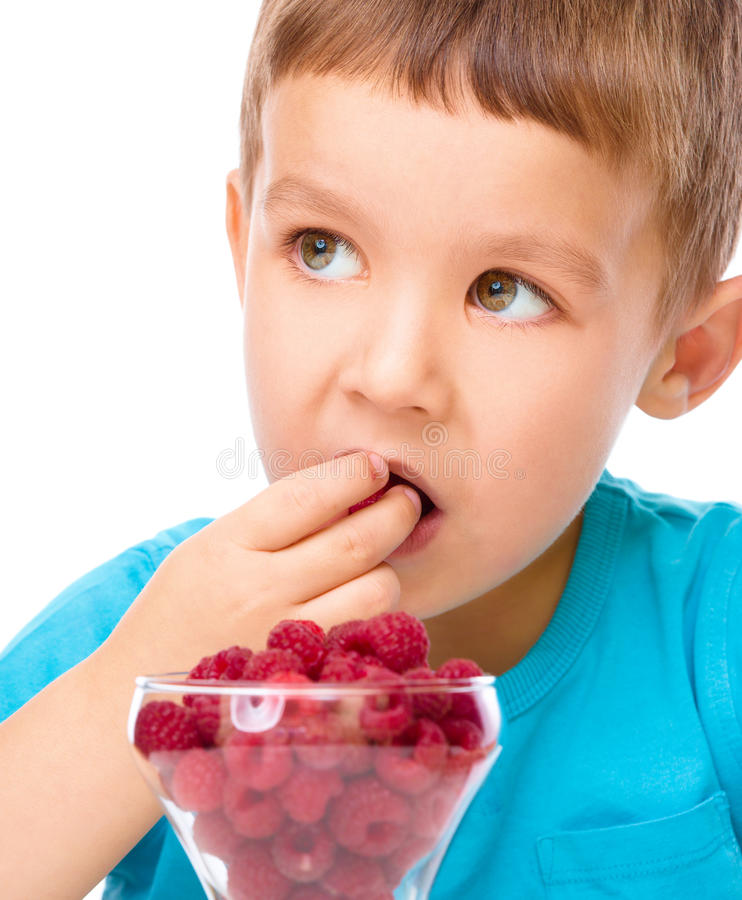Little boy with raspberries. Little boy is eating raspberries, isolated over white royalty free stock image