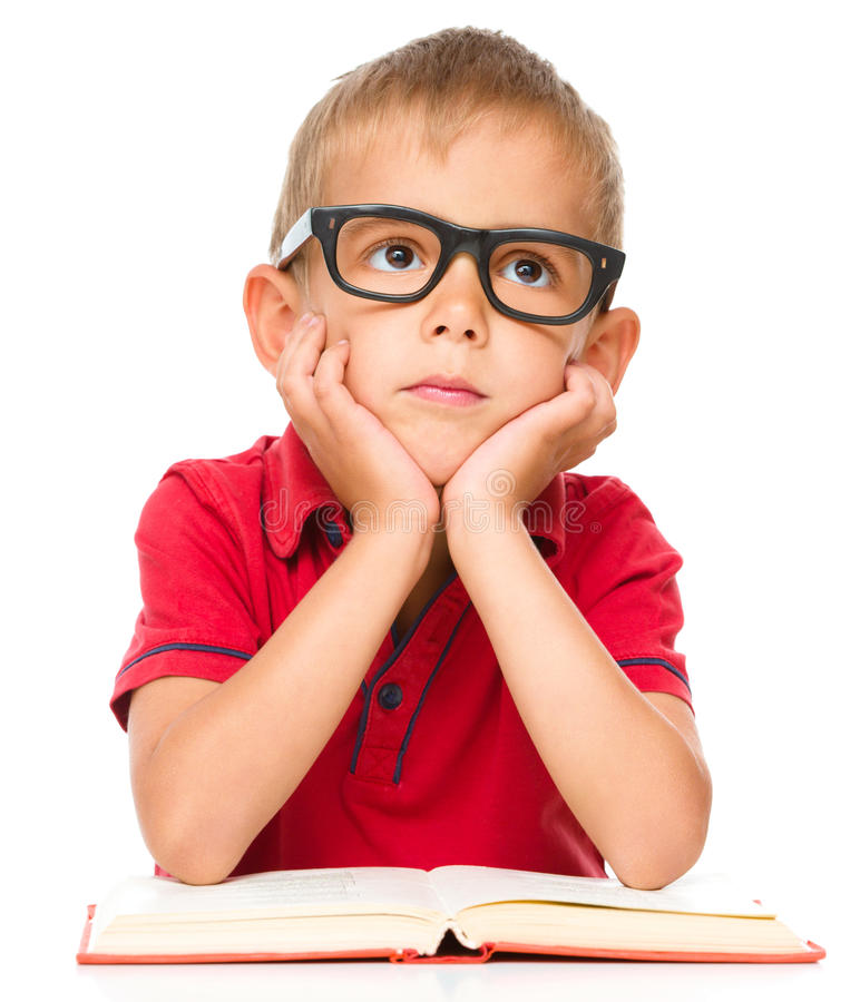 Little boy is reading a book. Cute little boy is reading a book while wearing glasses, isolated over white stock image