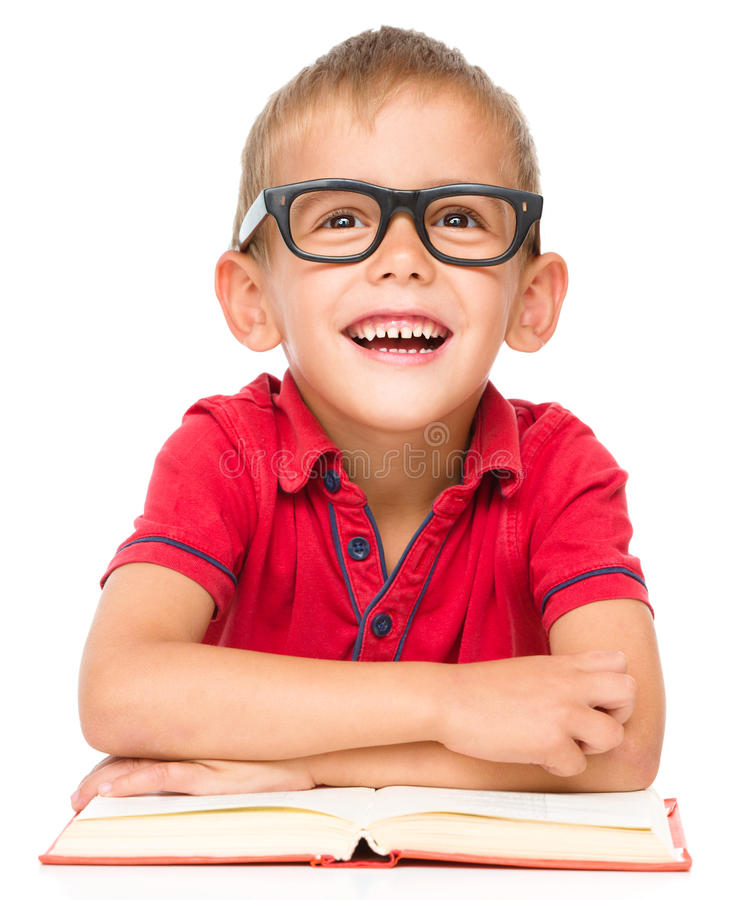 Little boy is reading a book. Cute little boy is reading a book while wearing glasses, isolated over white royalty free stock photography