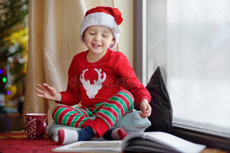 Little boy reading a book and drinking hot cocoa in decorated cozy living room. Happy kid on Christmas time royalty free stock images