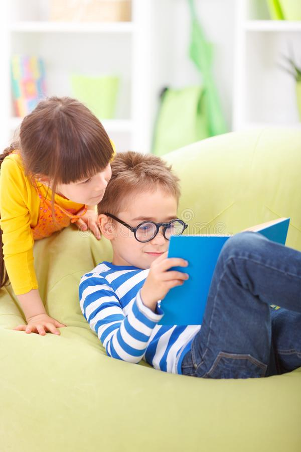 Little boy reading from book for his sister royalty free stock photos