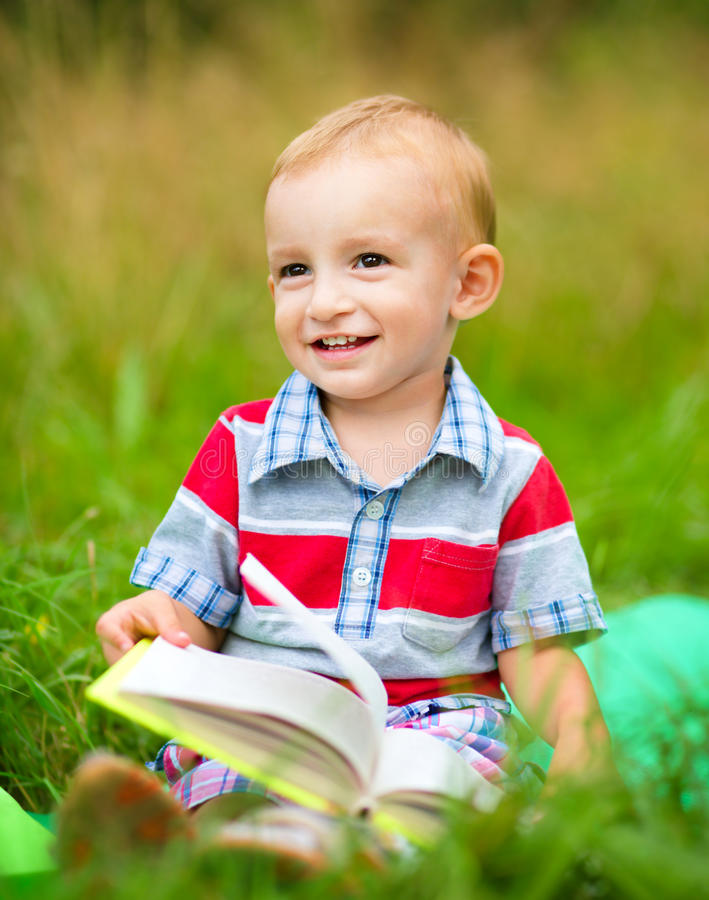 Little boy is reading book. While sitting on green grass outdoors royalty free stock photos