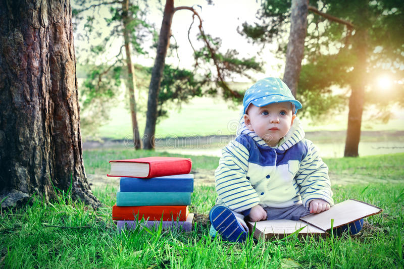 Little boy reading a book while sitting on the green grass in park. Stack of multicolored textbooks and cute baby. stock photo