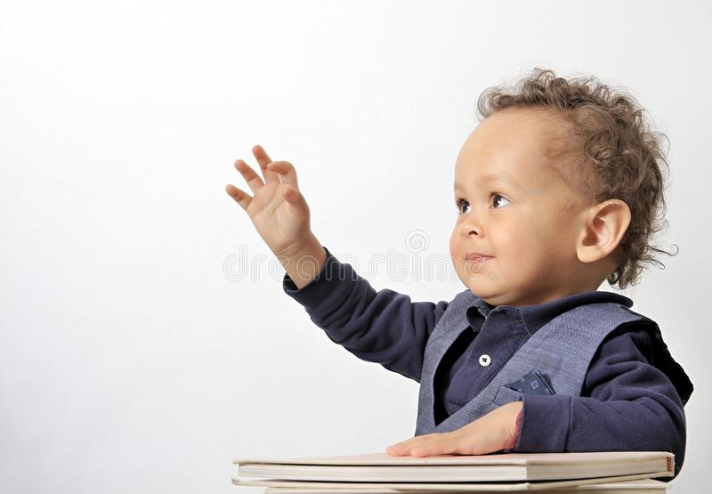 Little boy with reading books on a table at school stock photos
