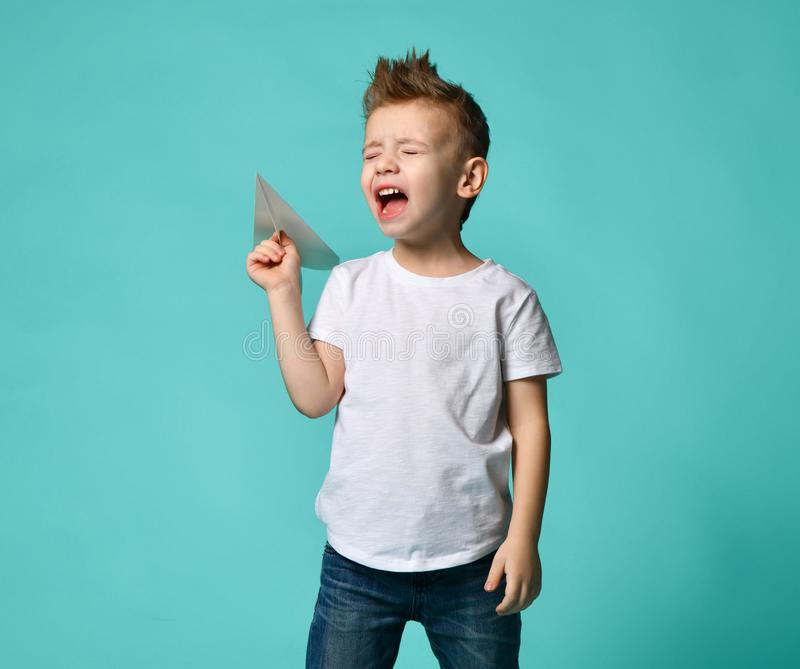 Little boy ready to launch a paper plane but cry with closed eyes. new step. Little boy in white t-shirt and blue jeans casual cry before launch a paper plane royalty free stock photo