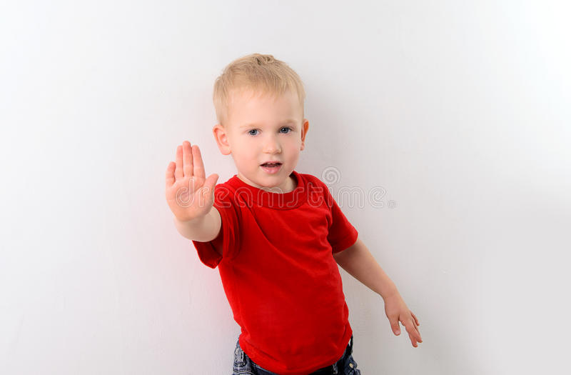 Little boy in red shirt showing stop sign stock photos
