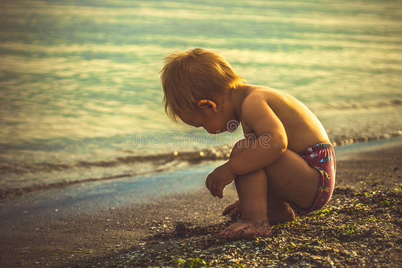 Little boy in red shorts played on the beach. In the sand stock photos