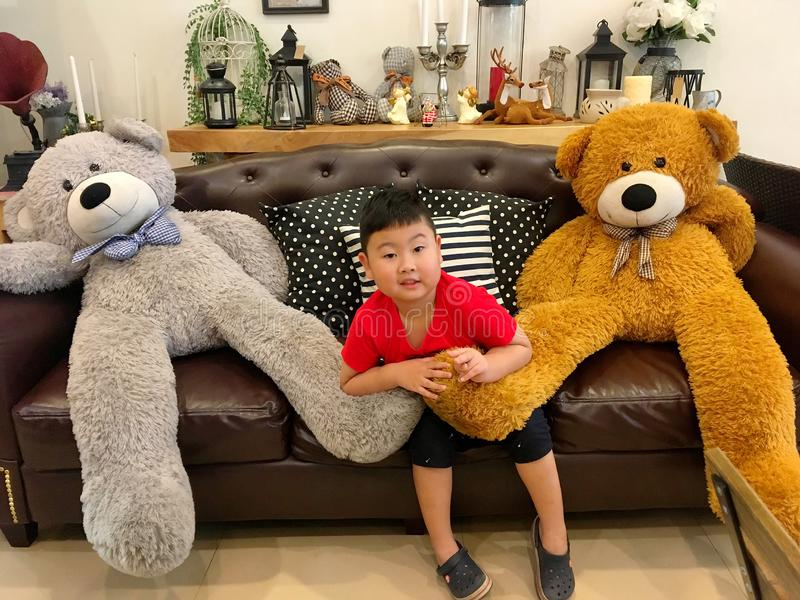 A little boy in red t-shirt and black shorts is sitting and playing with two teddy bears on the brown sofa in the living room. stock images