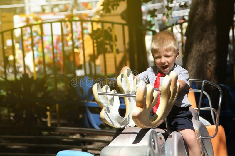 little boy with a red tie riding a carousel royalty free stock image