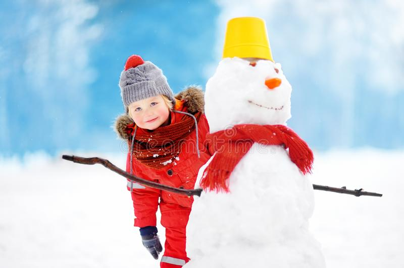 Little boy in red winter clothes having fun with snowman in snowy park royalty free stock photos