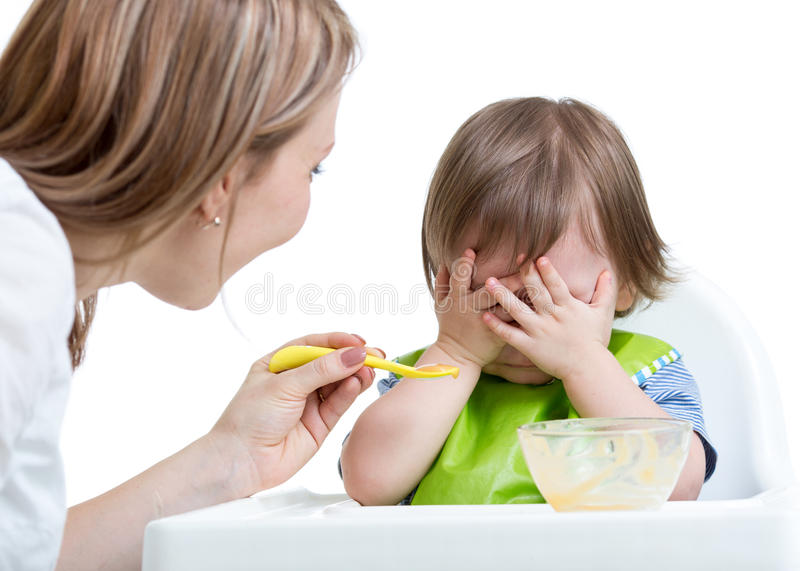 Little boy refuses to eat closing face by hands. Isolated on white stock photography