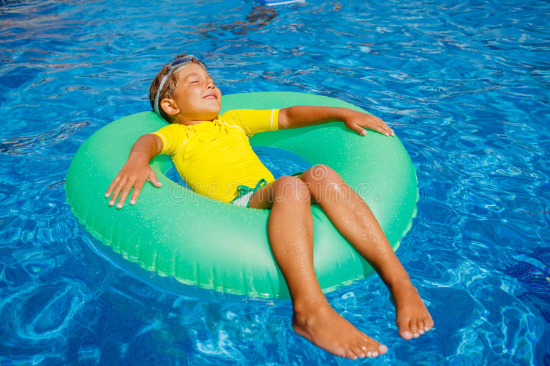 Little boy relax in pool stock photography