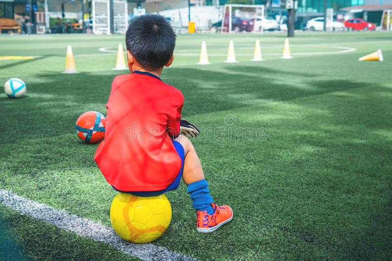 Little boy relaxing in soccer training field royalty free stock photography