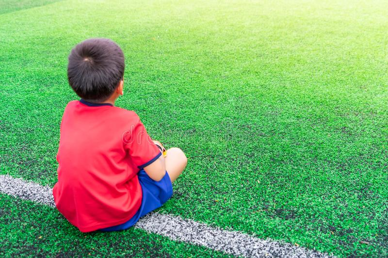 Little boy relaxing in soccer training field stock photography