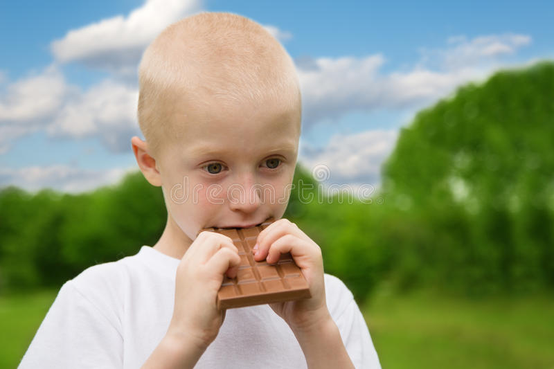 Little boy with relish eating chocolate. Outdoors stock photos