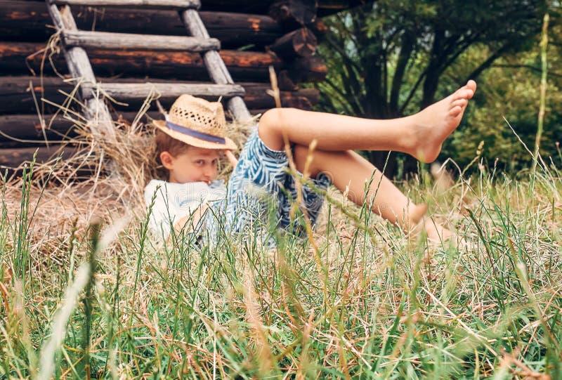 Little boy rest in green grass near the hayloft in garden royalty free stock photo