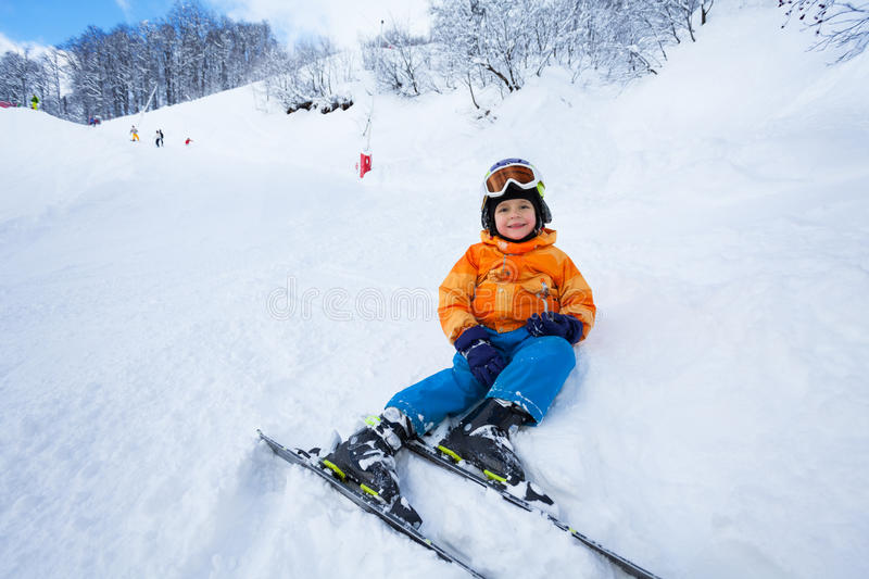 Little boy rest after ski lesson sitting in snow. Little cute boy with mountain ski rest on the piste wearing helmet royalty free stock photography