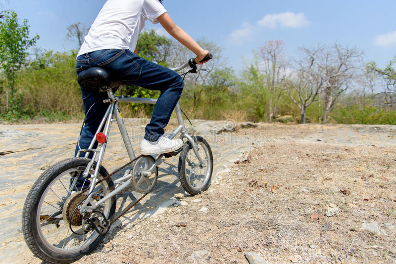Little boy ride bicycle on the rock road. royalty free stock image