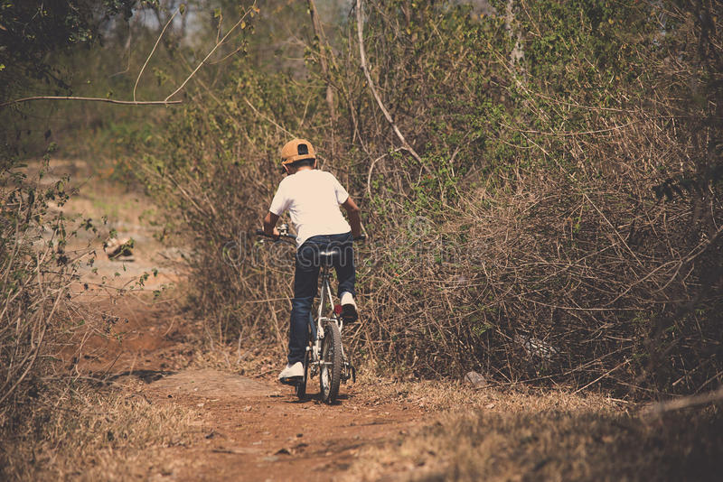 Little boy ride bicycle on the rock road. royalty free stock photos