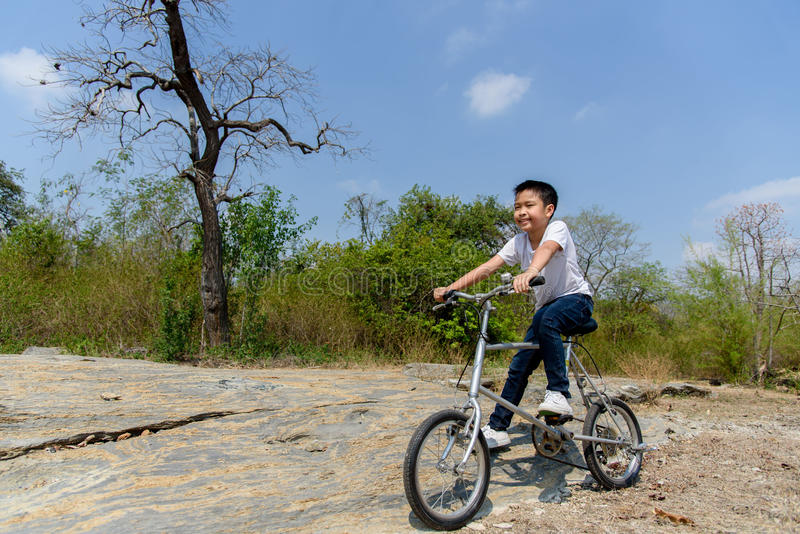 Little boy ride bicycle on the rock road. royalty free stock photography