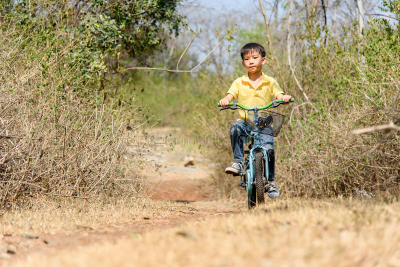 Little boy ride bicycle on the rock road. stock images