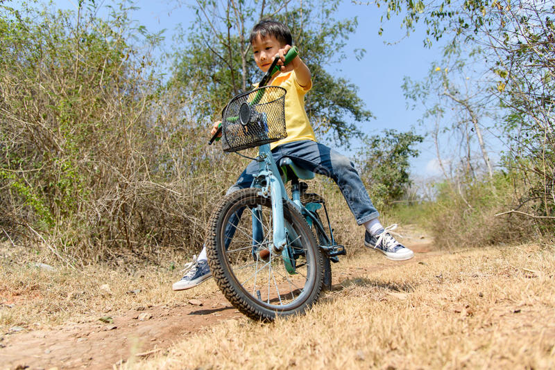Little boy ride bicycle on the rock road. stock photography