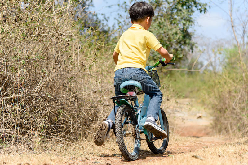 Little boy ride bicycle on the rock road. stock photo