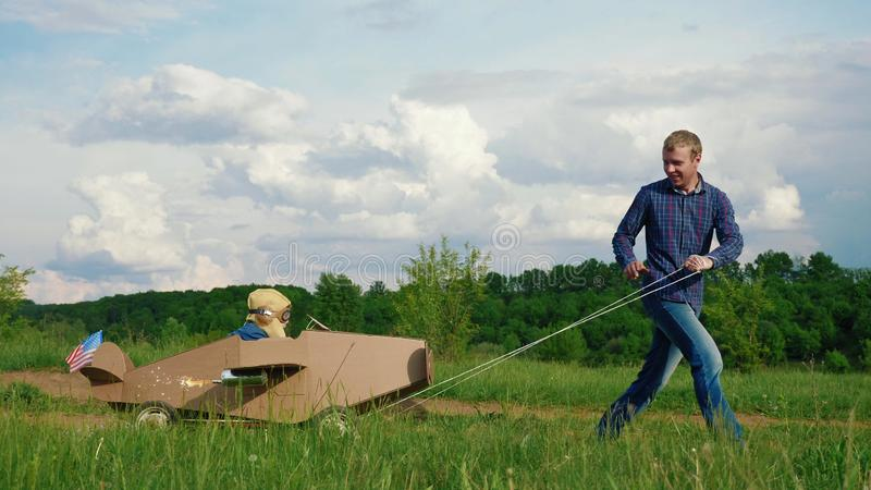 A little boy rides a homemade cardboard plane. Concept of friendly family. A little boy rides a homemade cardboard plane. Father rolling a little boy dressed as royalty free stock images