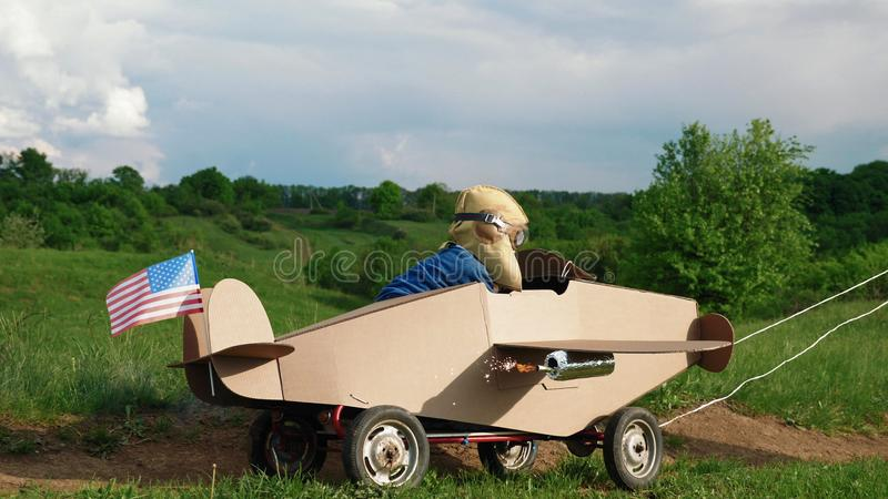 A little boy rides a homemade cardboard plane. Father rolling a little boy dressed as a pilot on a cardboard airplane on nature. Concept of friendly family stock photos