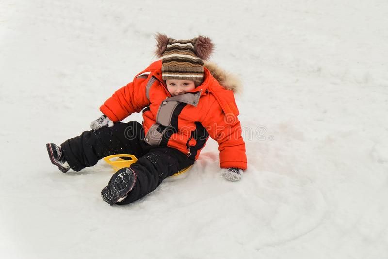 Little boy rides on an ice-boat from a snow slide. Sledding snow saucer - winter childrens fun. Winter activity royalty free stock photos