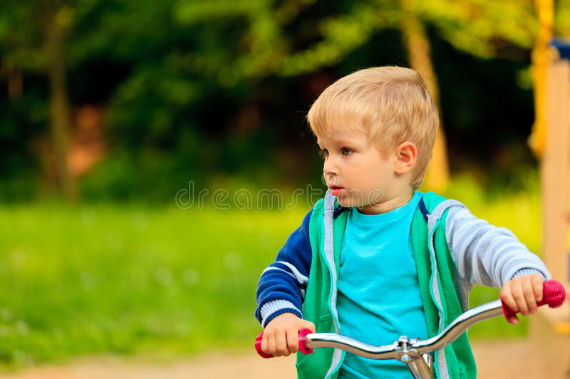 Little boy riding bike in the park royalty free stock image