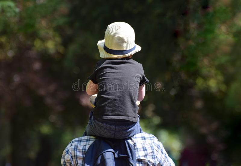 A little boy riding on his father`s shoulders royalty free stock images