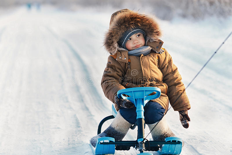 Little boy riding his kids snowmobile winter snow-covered road royalty free stock image