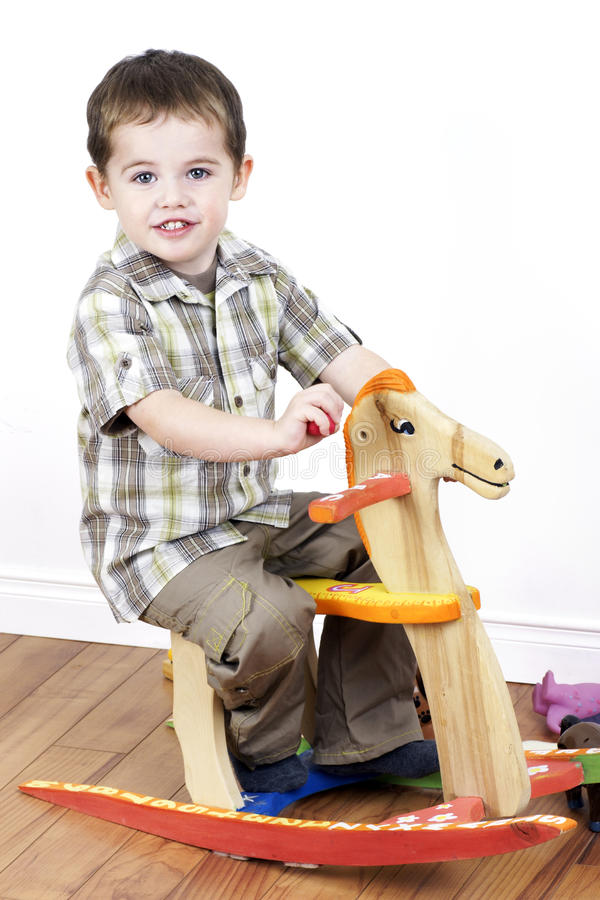 Download Little Boy Riding A Rocking Horse Stock Image - Image: 21934901
