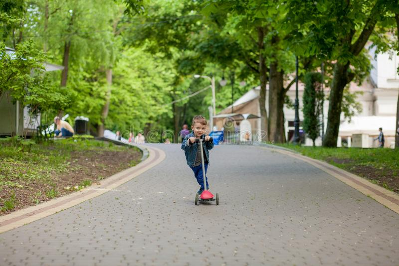 Little boy riding scooter in city park in aummer. Kids sports outdoors. Happy child playing with his scooter. Kid learn to ride. Scooter in park. Happy stock images