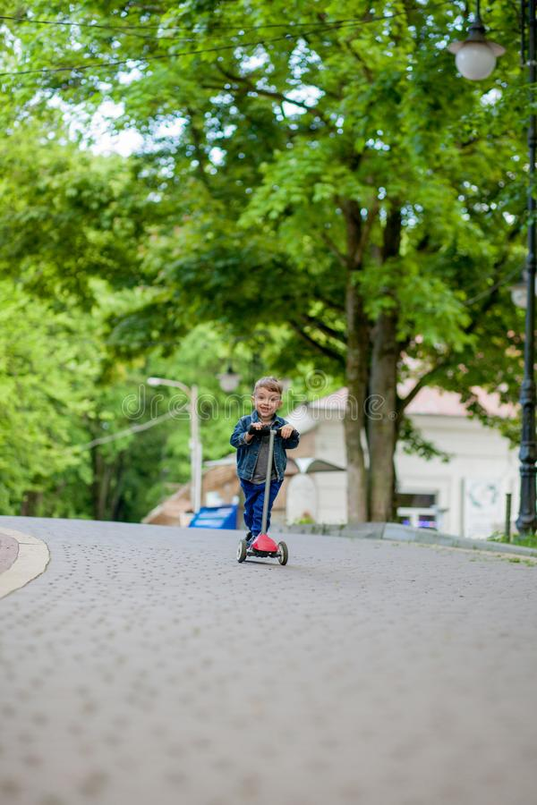 Little boy riding scooter in city park in aummer. Kids sports outdoors. Happy child playing with his scooter. Kid learn to ride. Scooter in park. Happy stock photos