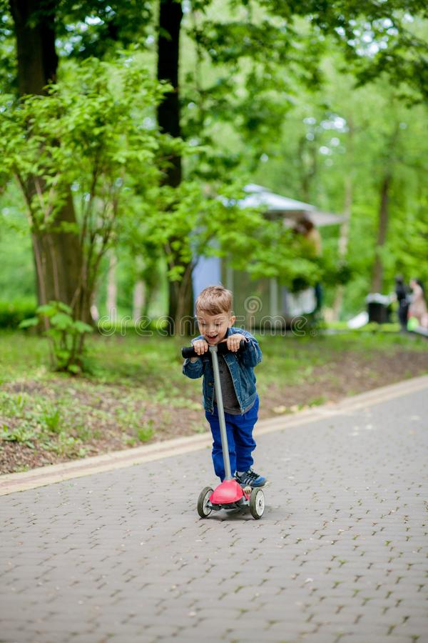 Little boy riding scooter in city park in aummer. Kids sports outdoors. Happy child playing with his scooter. Kid learn to ride. Scooter in park. Happy royalty free stock images