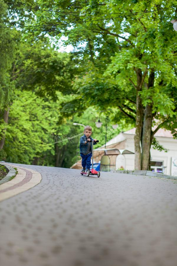 Little boy riding scooter in city park in aummer. Kids sports outdoors. Happy child playing with his scooter. Kid learn to ride. Scooter in park. Happy royalty free stock image