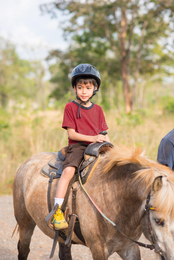 Little boy riding training horse royalty free stock images
