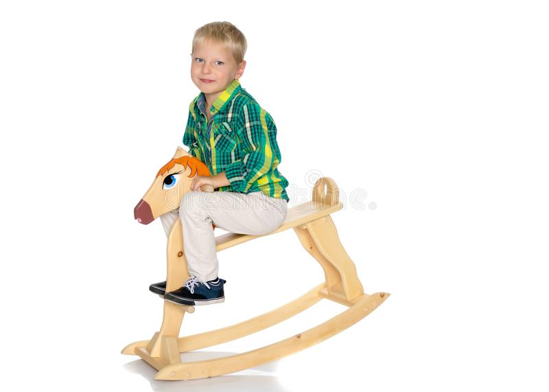 A little boy is riding a wooden horse stock photography