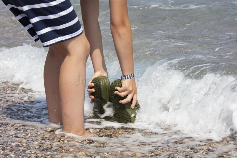 Little boy rinsing green sandals in the ocean in Rhodes, Greece. royalty free stock photo
