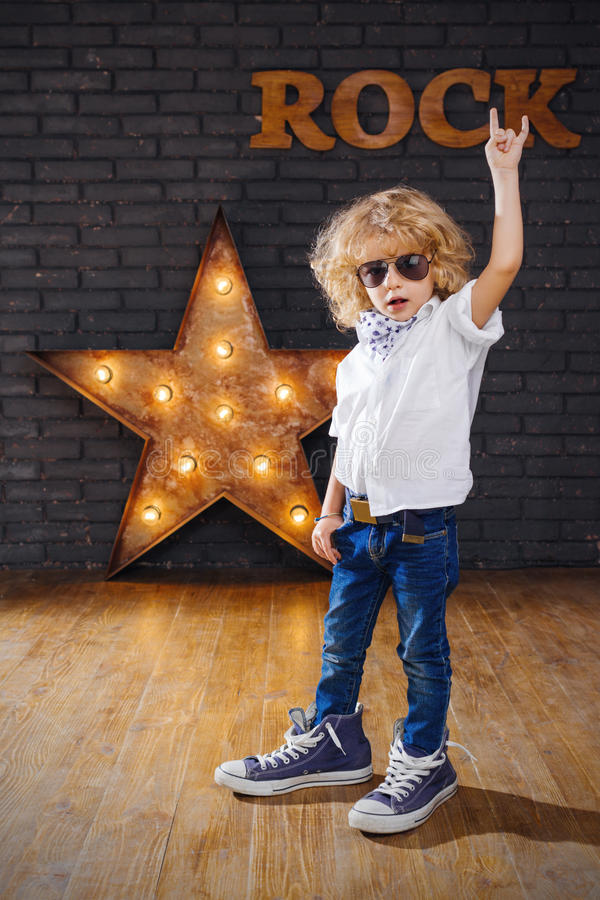 Free Little Boy Rock Star Giving The Rock And Roll Sign Royalty Free Stock Images - 69088809