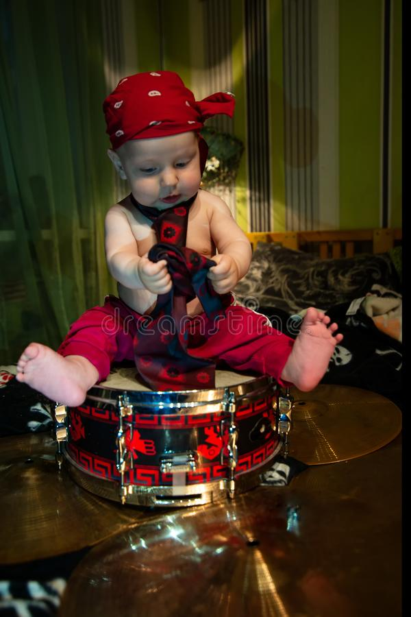 Little boy rocker drummer in red bandana and with drum stock photo