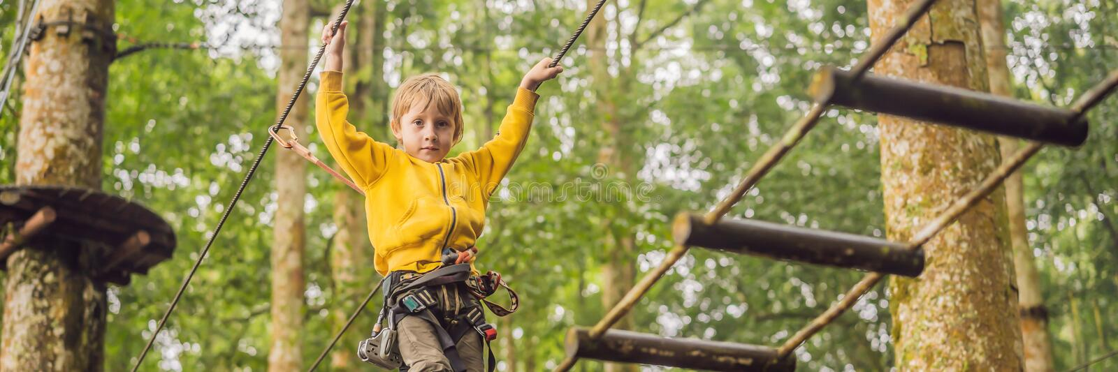 Little boy in a rope park. Active physical recreation of the child in the fresh air in the park. Training for children royalty free stock image