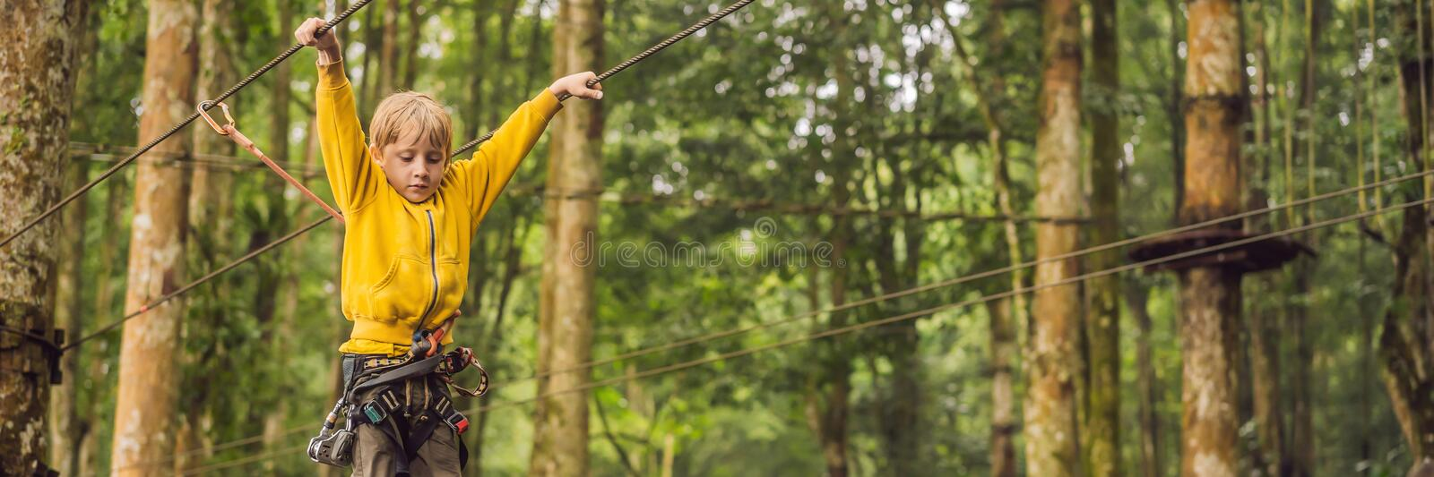 Little boy in a rope park. Active physical recreation of the child in the fresh air in the park. Training for children stock images